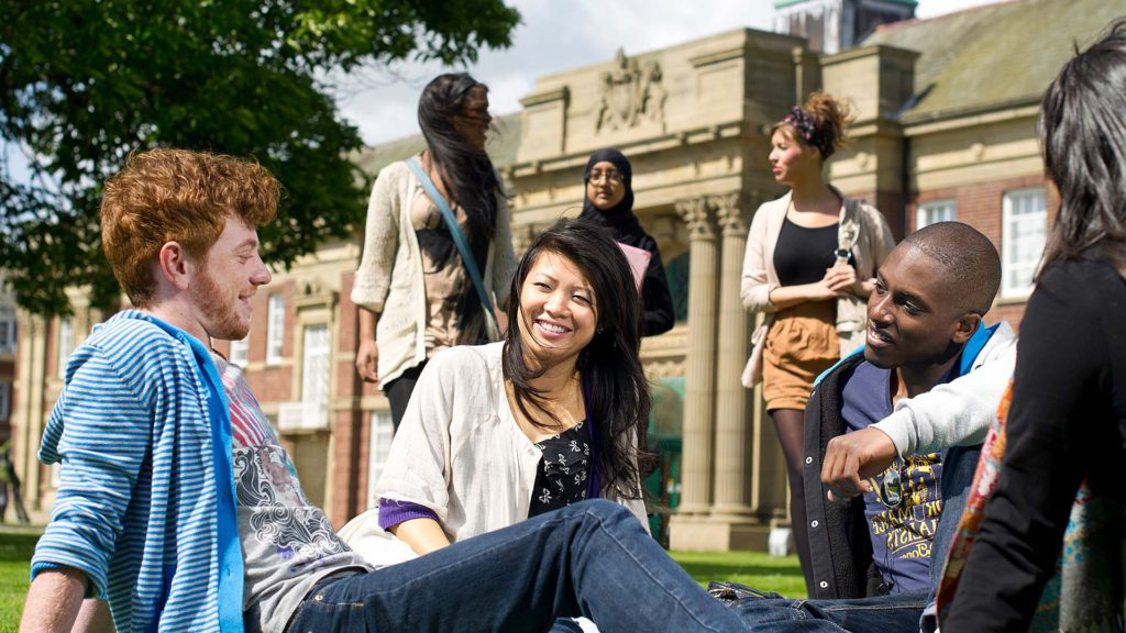 A number of international students sitting on the lawn in front of the main building