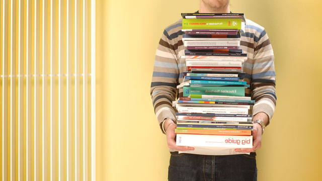 A person carrying a selection of books