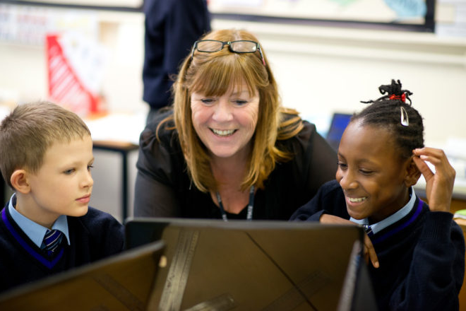 Junior school teacher working with two pupils