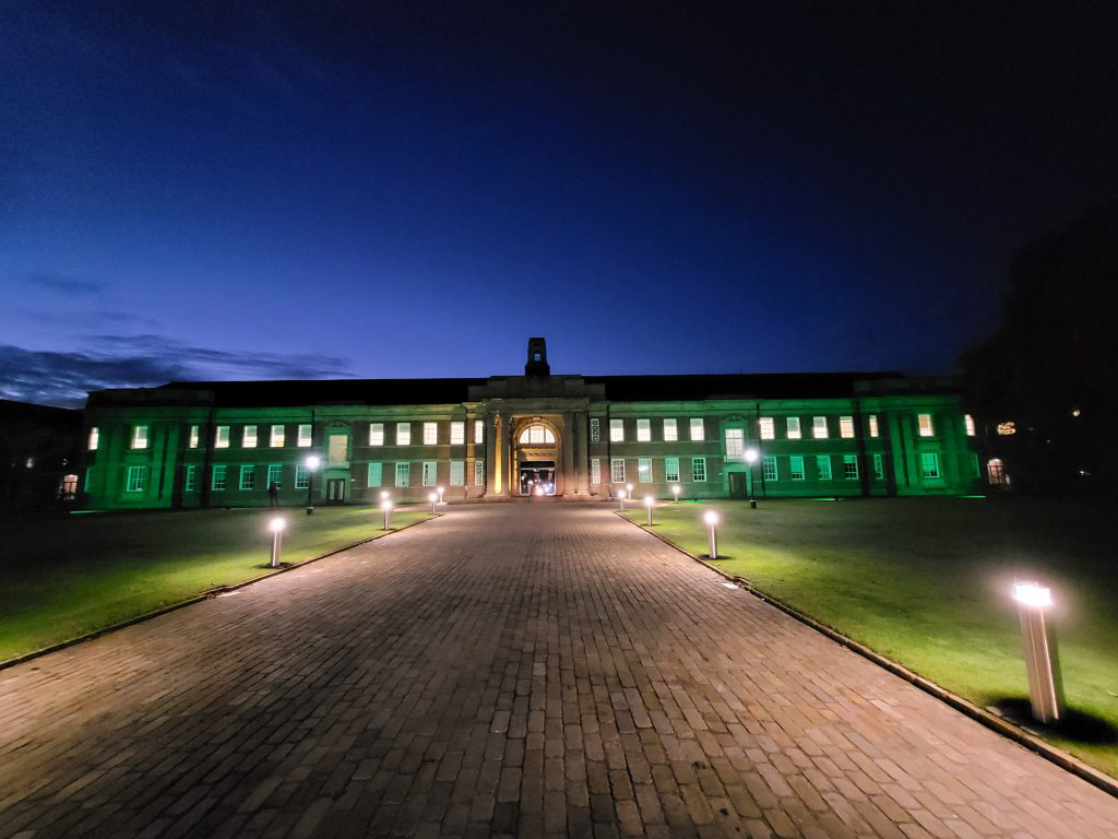 A picture of Edge Hill's main campus lit up in green.