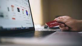 Hand holding a payment card in front of a laptop
