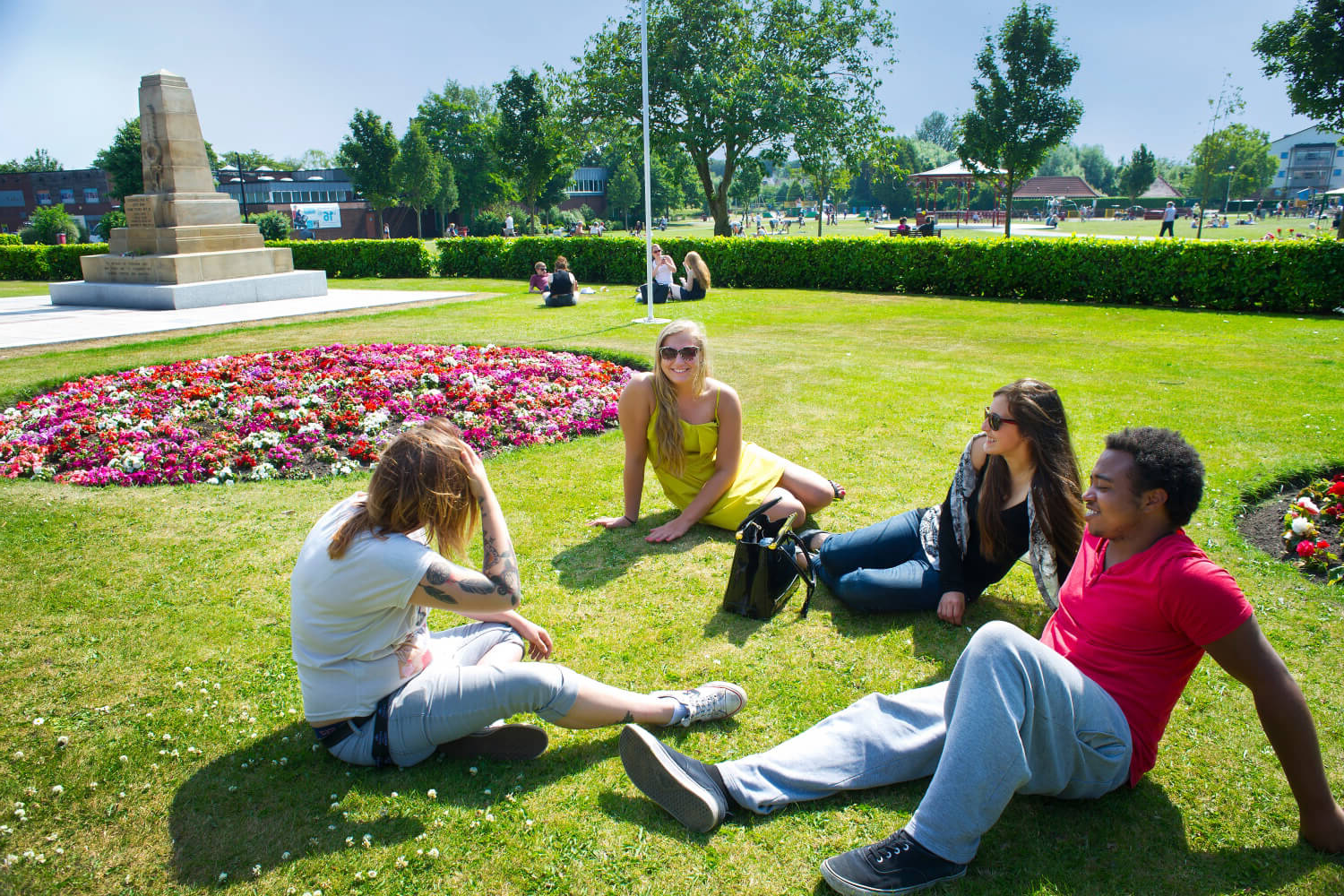 Four students relax on the grass in C要么onation Park in 奥姆斯科克.