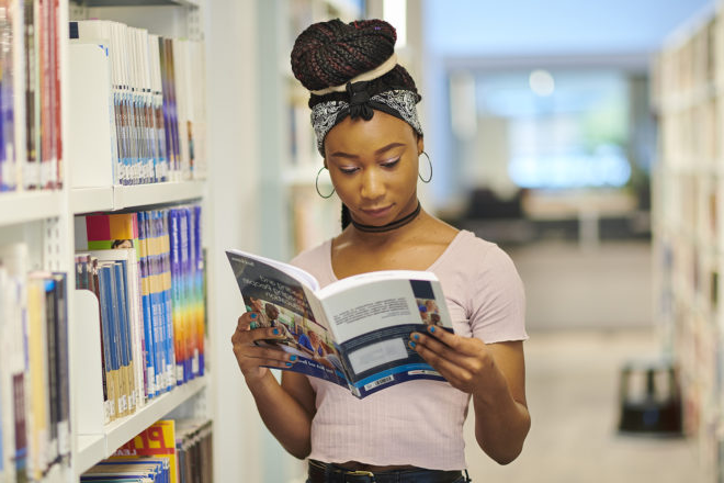 A student reads a book while browsing the shelves in the University library in the Catalyst building.