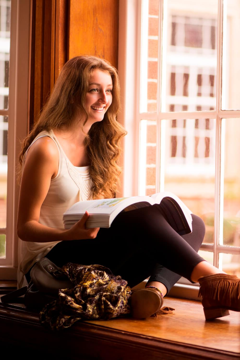 A student sits on a window sill in Sages restaurant 和 looks out over the Quad while reading a geography book.
