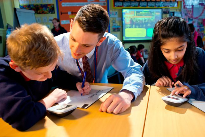 A trainee teacher observes two primary school pupils as they use calculators to complete a test.
