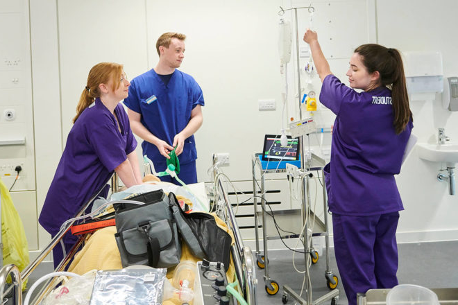 Three student operating department practitioners attend a patient on a trolley with one student squeezing a drip bag.