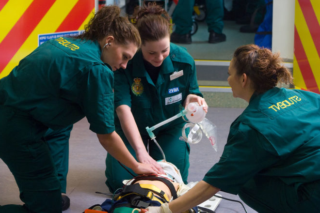 Three Paramedic trainees hone their skills on a mannequin on the floor outside an ambulance simulator.