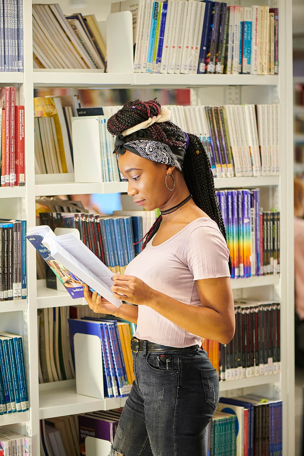 A student flicks through a book while stood near shelves of books in the University library in the Catalyst building.