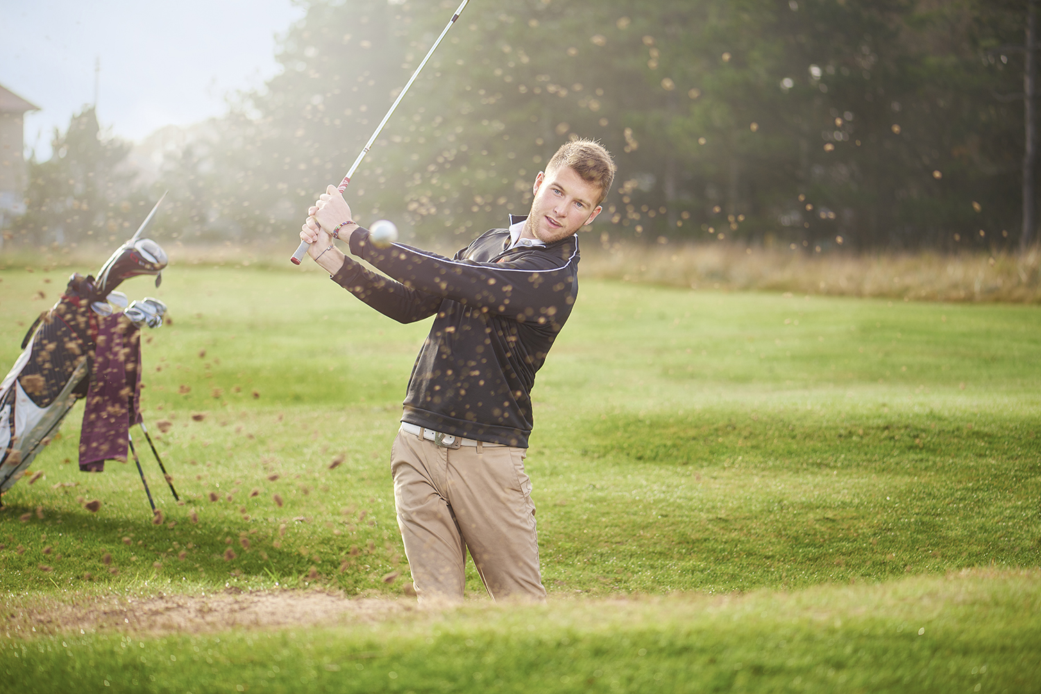 A student plays a shot on a golf course.